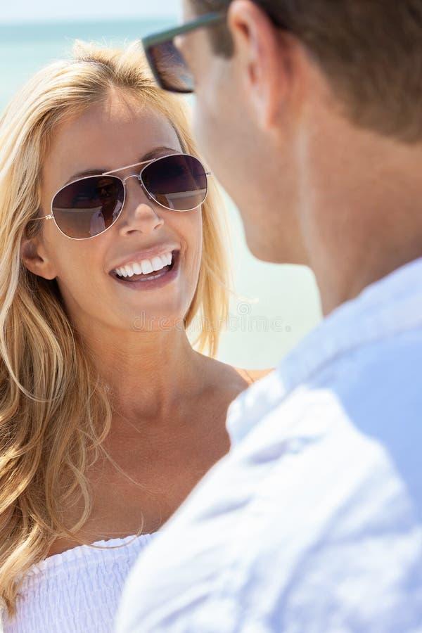 Ζεύγος ανδρών γυναικών που φορά τα γυαλιά ηλίου σε μια παραλία στοκ φωτογραφία