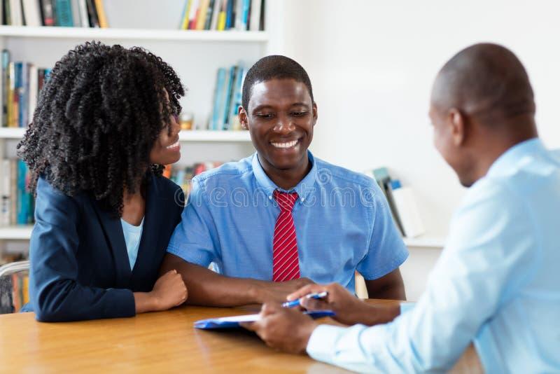 Ζεύγος αφροαμερικάνων με τη σύμβαση του κτηματομεσίτη στοκ εικόνες