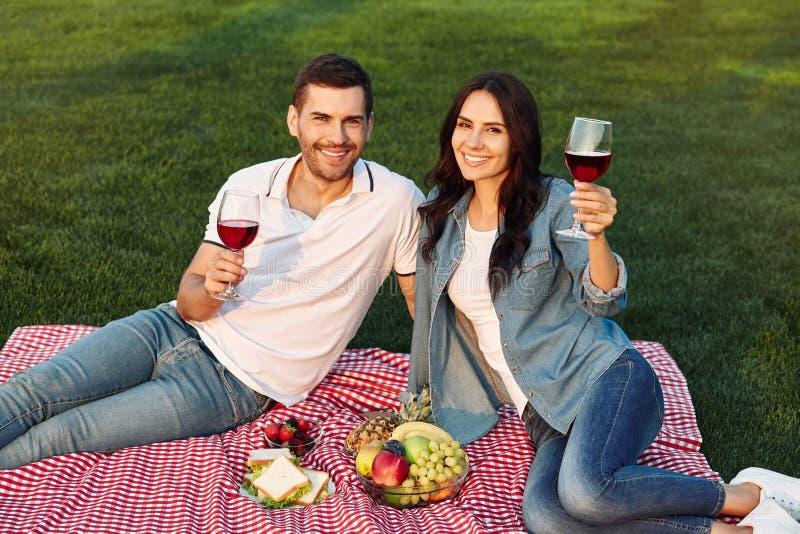 Ζεύγος ενθαρρυντικό με τα γυαλιά κρασιού στο πάρκο στοκ εικόνες