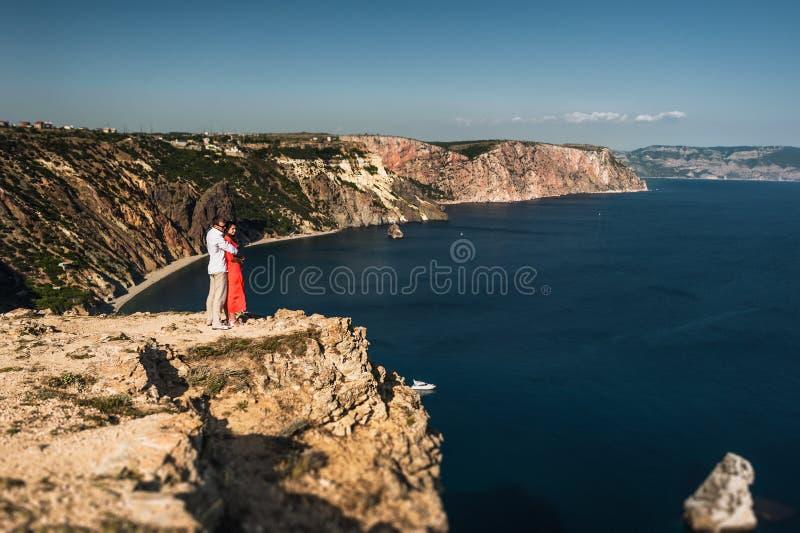 Ζεύγος ερωτευμένο στο ηλιοβασίλεμα θαλασσίως honeymoon Ταξίδι μήνα του μέλιτος Αγόρι και κορίτσι στη θάλασσα διακινούμενη γυναίκα στοκ φωτογραφία με δικαίωμα ελεύθερης χρήσης