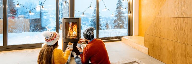 Ζεύγος κοντά στην εστία στο σπίτι κατά τη διάρκεια του χειμώνα στοκ φωτογραφία