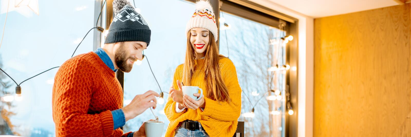 Ζεύγος με τα ζεστά ποτά κοντά στην εστία κατά τη διάρκεια του χειμώνα στοκ φωτογραφία με δικαίωμα ελεύθερης χρήσης
