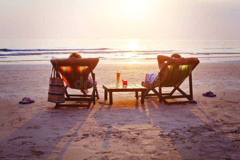 Ζεύγος με τα κοκτέιλ που χαλαρώνει στην παραλία στοκ εικόνες