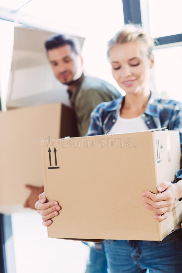 Ζεύγος με τα κουτιά από χαρτόνι στο καινούργιο σπίτι στοκ φωτογραφίες