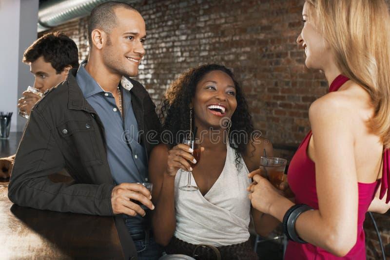 Ζεύγος με τα ποτά εκμετάλλευσης φίλων στο φραγμό στοκ εικόνα