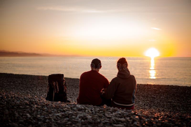 Ζεύγος με τα σακίδια πλάτης που κάθονται στην παραλία και που εξετάζουν τη θάλασσα στοκ φωτογραφία