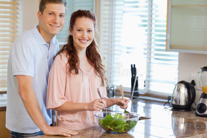 Ζεύγος με τη σαλάτα στην κουζίνα στοκ εικόνα