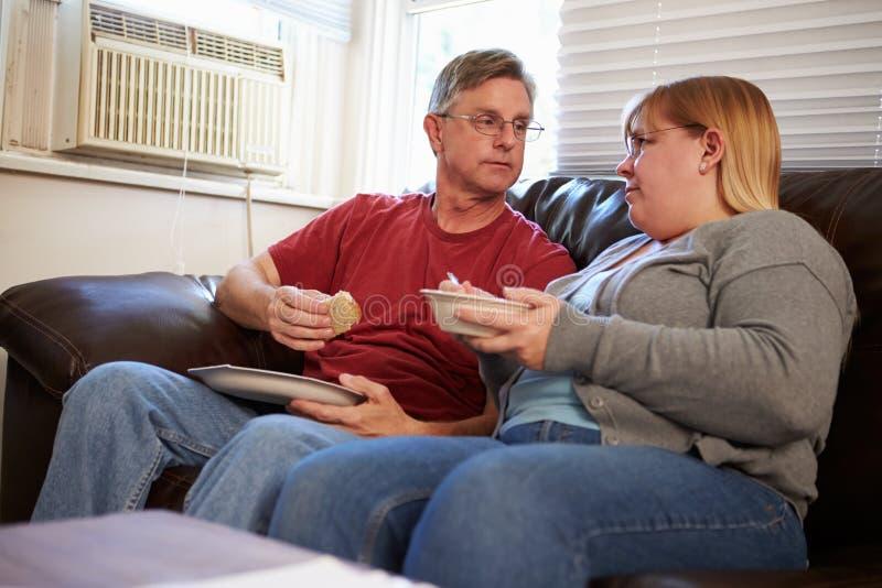 Ζεύγος με τη φτωχή συνεδρίαση διατροφής στον καναπέ που τρώει το γεύμα στοκ φωτογραφία με δικαίωμα ελεύθερης χρήσης