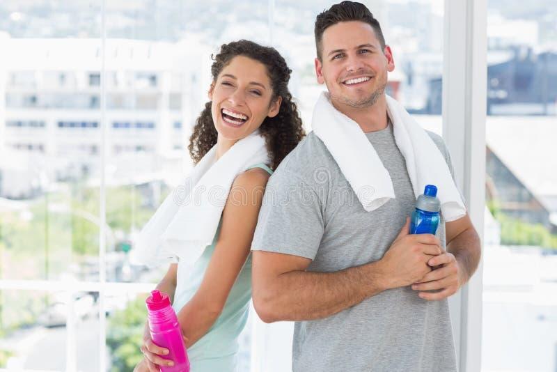 Ζεύγος με τις πετσέτες και τα μπουκάλια νερό στη γυμναστική στοκ φωτογραφία με δικαίωμα ελεύθερης χρήσης