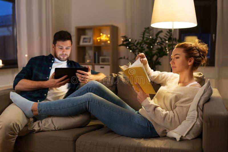 Ζεύγος με τον υπολογιστή και το βιβλίο ταμπλετών στο σπίτι στοκ εικόνες με δικαίωμα ελεύθερης χρήσης
