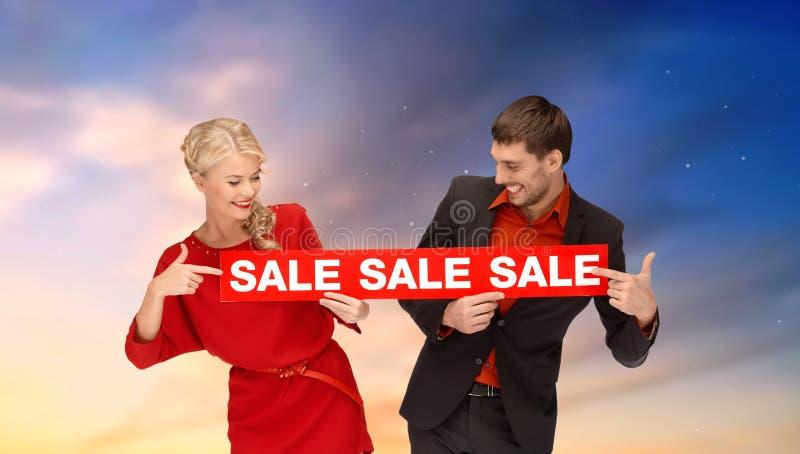 Ζεύγος με το κόκκινο σημάδι πώλησης στοκ εικόνες