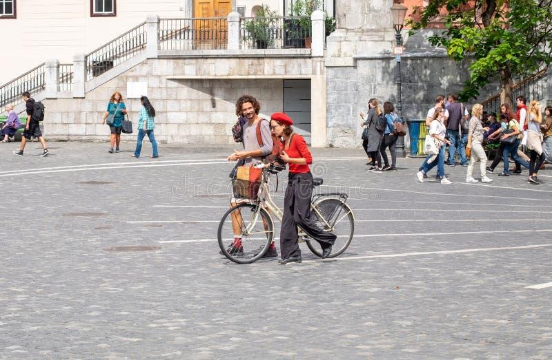 Ζεύγος με το ποδήλατο, που περπατά στο κεντρικό τετράγωνο στο Λουμπλιάνα, η πρωτεύουσα της Σλοβενίας στοκ φωτογραφία με δικαίωμα ελεύθερης χρήσης