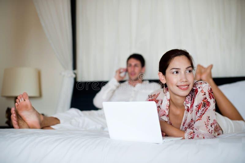Ζεύγος με το lap-top και το τηλέφωνο στοκ φωτογραφία