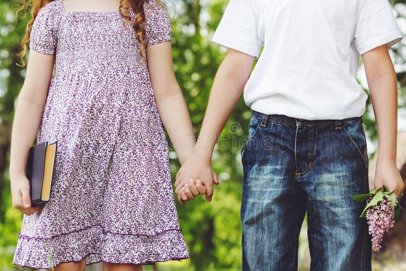 Ζεύγος, μικρό κορίτσι και αγόρι εφήβων που κρατούν το χέρι του Πρώτη αγάπη ή στοκ εικόνες