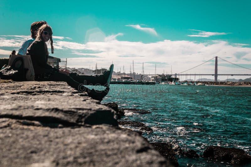 Ζεύγος μπροστά από τη χρυσή γέφυρα πυλών στο Σαν Φρανσίσκο, Californ στοκ εικόνες