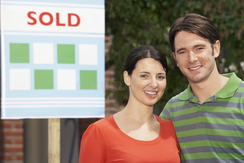 Ζεύγος μπροστά από το νέο σπίτι με το πωλημένο σημάδι στοκ εικόνες