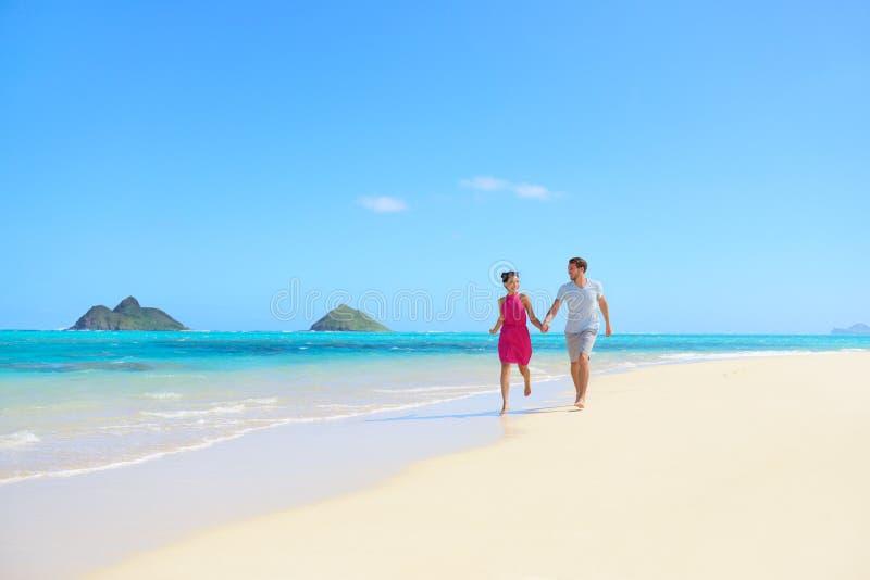 Ζεύγος παραλιών ευτυχές έχοντας τη διασκέδαση στο μήνα του μέλιτος της Χαβάης στοκ φωτογραφία με δικαίωμα ελεύθερης χρήσης
