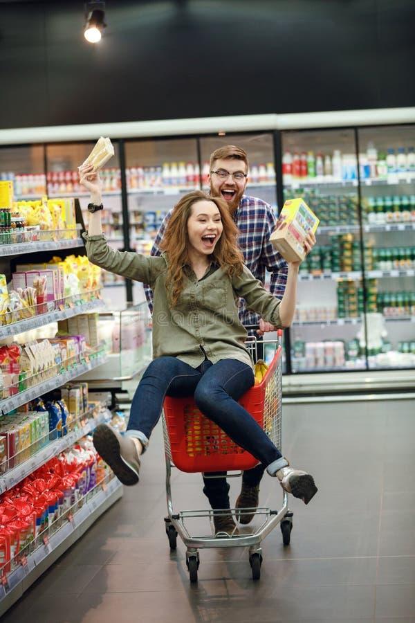 Ζεύγος που έχει τη διασκέδαση με το κάρρο αγορών στην υπεραγορά στοκ φωτογραφία με δικαίωμα ελεύθερης χρήσης