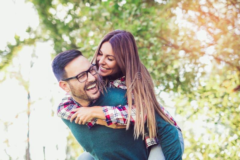 Ζεύγος που έχει τον άνδρα διασκέδασης που δίνει piggyback στη γυναίκα στοκ εικόνα