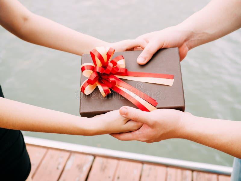 Ζεύγος που δίνει ένα κιβώτιο δώρων ο ένας στον άλλο Ευτυχής σχέση στο OU στοκ εικόνα