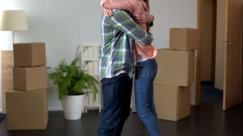 Ζεύγος που αγκαλιάζει ακριβώς στο αγορασμένο διαμέρισμα, ανοιγμένα πράγματα γύρω στα κιβώτια στοκ φωτογραφία
