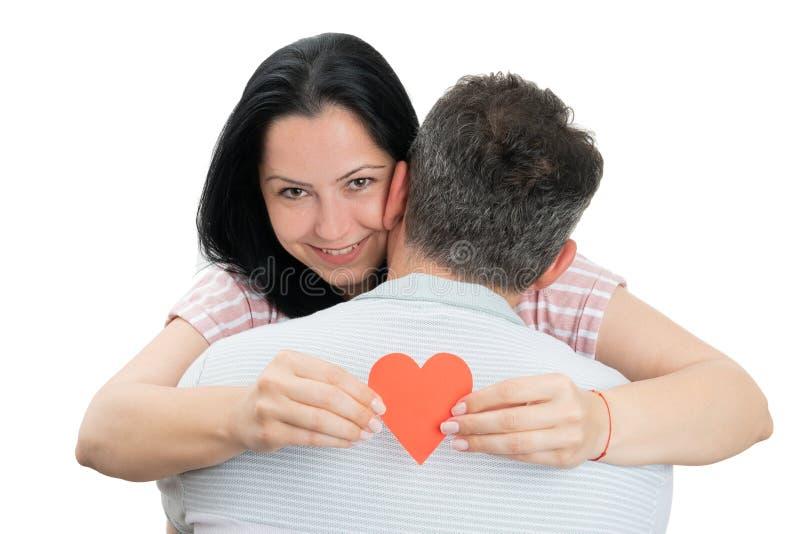 Ζεύγος που αγκαλιάζει και που κρατά την κόκκινη καρδιά στοκ φωτογραφία με δικαίωμα ελεύθερης χρήσης