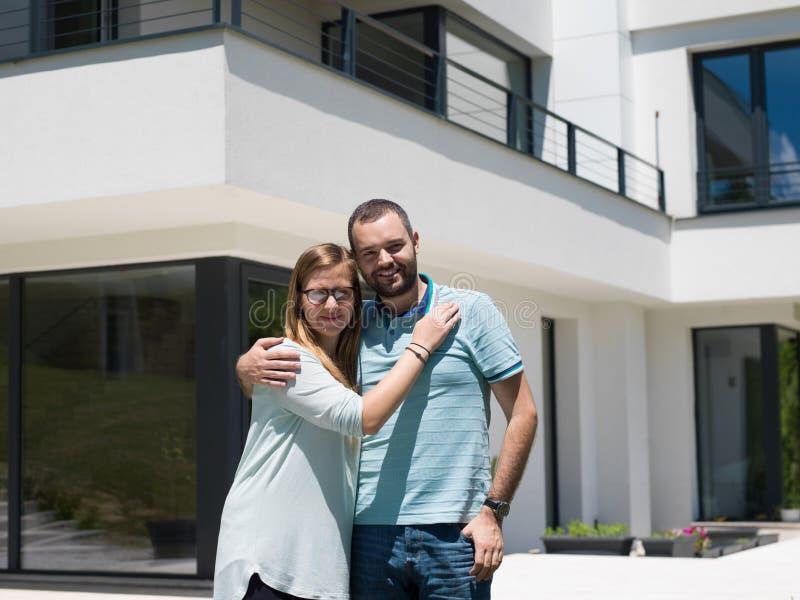 Ζεύγος που αγκαλιάζει μπροστά από το νέο σπίτι πολυτέλειας στοκ εικόνες