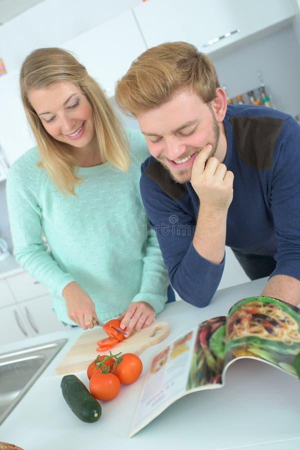 Ζεύγος που αγκαλιάζει στην κουζίνα ελέγχοντας το βιβλίο συνταγής στοκ εικόνες