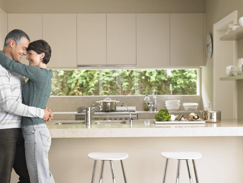 Ζεύγος που αγκαλιάζει στην κουζίνα στοκ φωτογραφία