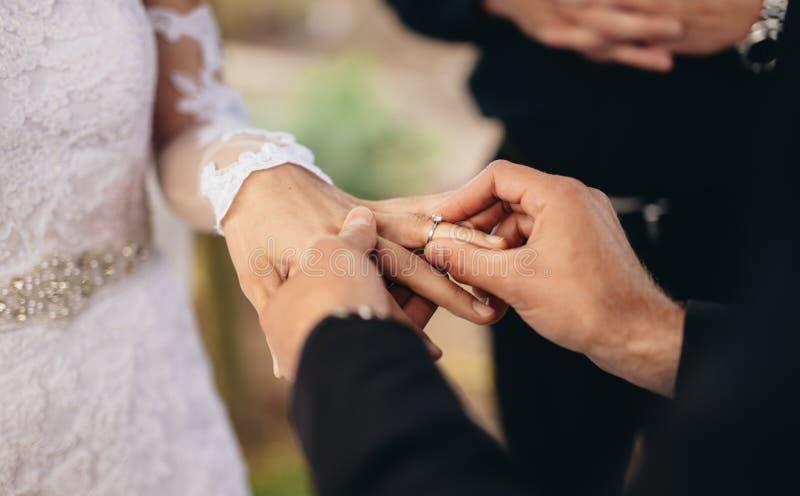Ζεύγος που ανταλλάσσει τα γαμήλια δαχτυλίδια στοκ εικόνες με δικαίωμα ελεύθερης χρήσης