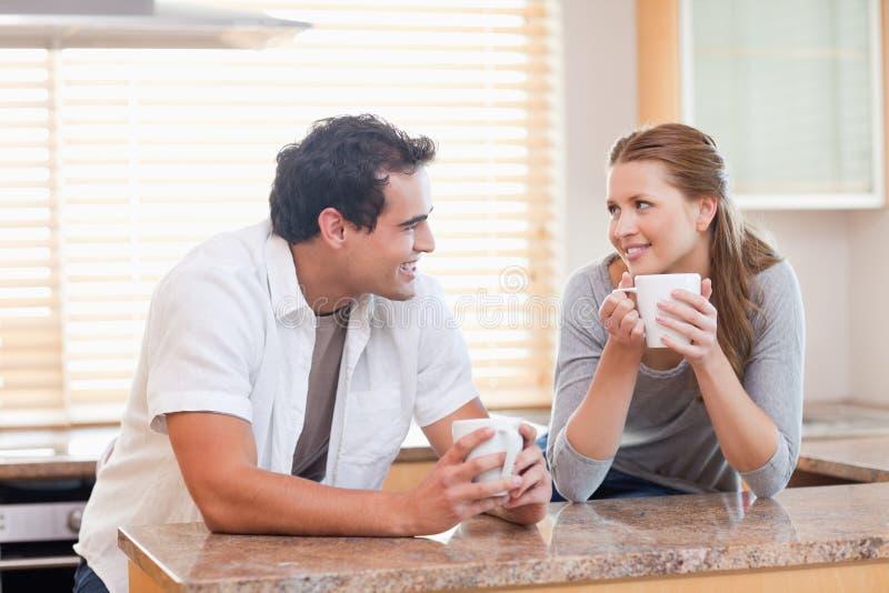 Ζεύγος που απολαμβάνει τον καφέ στην κουζίνα από κοινού στοκ φωτογραφία