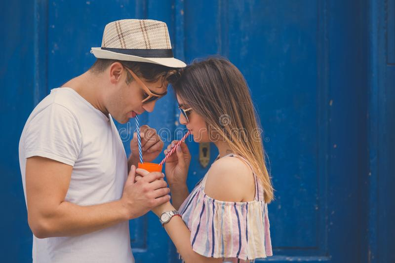 Ζεύγος που απολαμβάνει το χυμό από ένα γυαλί με δύο άχυρα κατανάλωσης στοκ εικόνες με δικαίωμα ελεύθερης χρήσης