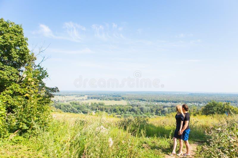 Ζεύγος που απολαμβάνει έναν περίπατο μέσω του εδάφους χλόης και που κοιτάζει μακριά στοκ εικόνα