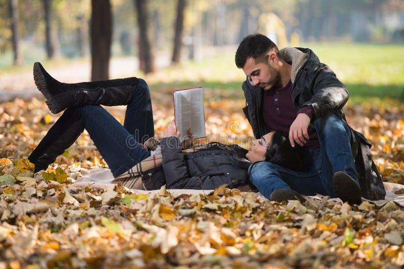 Ζεύγος που απολαμβάνει την ανάγνωση βιβλίων στο πάρκο φθινοπώρου στοκ φωτογραφία με δικαίωμα ελεύθερης χρήσης