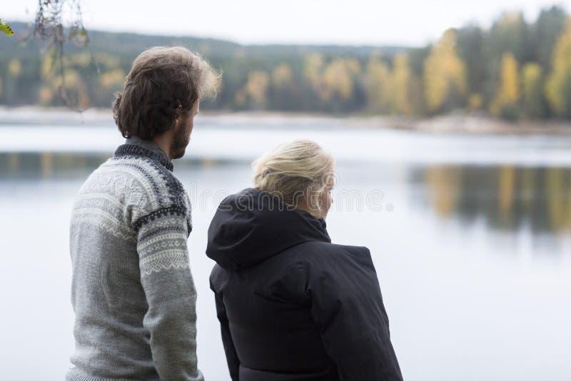 Ζεύγος που απολαμβάνει τη θέα λιμνών από τη θέση για κατασκήνωση στοκ εικόνες με δικαίωμα ελεύθερης χρήσης