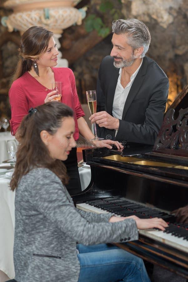 Ζεύγος που απολαμβάνει τη σαμπάνια γυαλιού ενώ η γυναίκα παίζει το πιάνο στοκ εικόνες