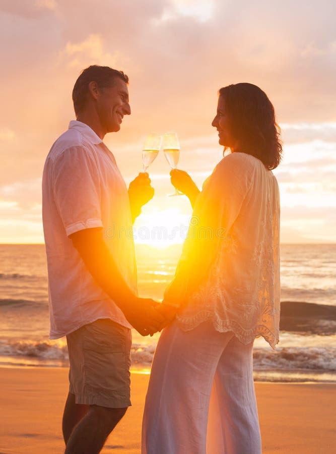 Ζεύγος που απολαμβάνει το γυαλί Champene στην παραλία στο ηλιοβασίλεμα στοκ φωτογραφία με δικαίωμα ελεύθερης χρήσης