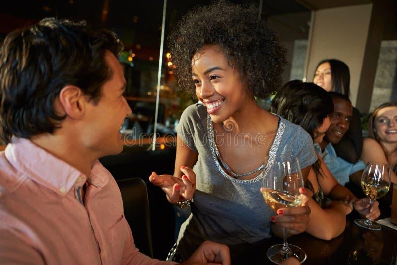 Ζεύγος που απολαμβάνει το ποτό στο φραγμό με τους φίλους στοκ εικόνα