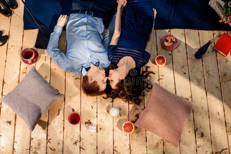 Ζεύγος που βρίσκεται στο ξύλινο πάτωμα με τα μαξιλάρια και τα γλυκά στοκ φωτογραφία