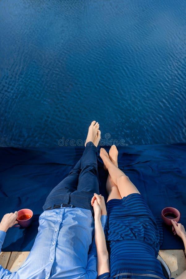 Ζεύγος που βρίσκεται στο πεζούλι κοντά στο μπλε νερό στοκ εικόνες