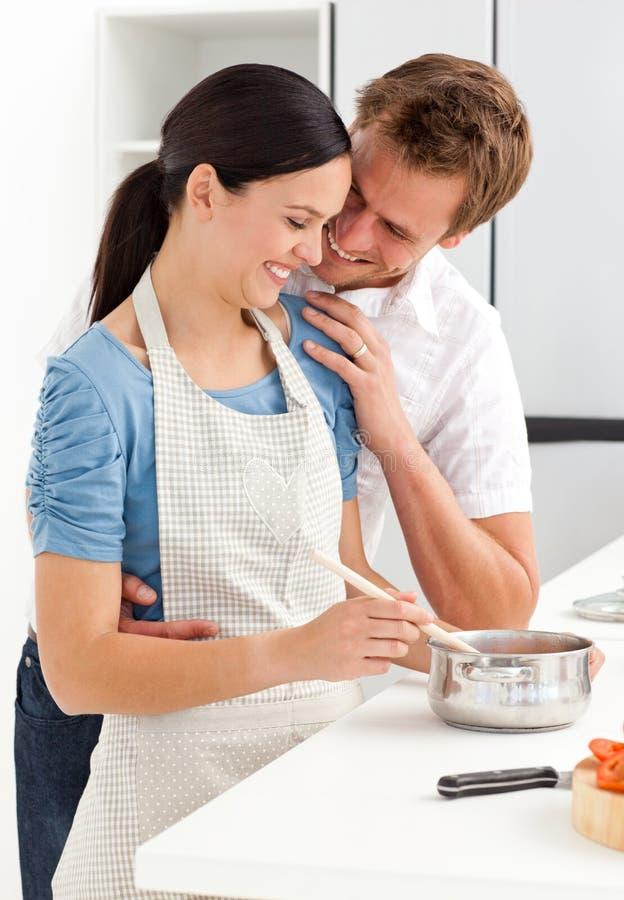 Ζεύγος που γελά προετοιμάζοντας μια σάλτσα στοκ φωτογραφίες