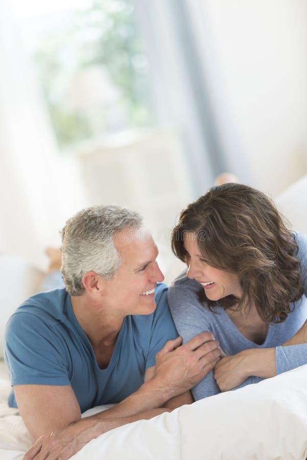 Ζεύγος που εξετάζει μεταξύ τους χαλαρώνοντας στο κρεβάτι στοκ εικόνα με δικαίωμα ελεύθερης χρήσης