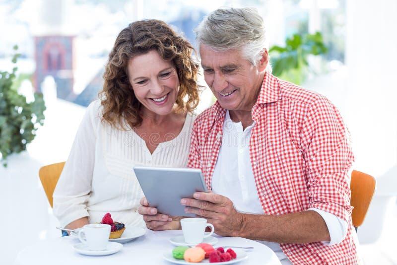 Ζεύγος που εξετάζει στον υπολογιστή ταμπλετών το εστιατόριο στοκ φωτογραφία