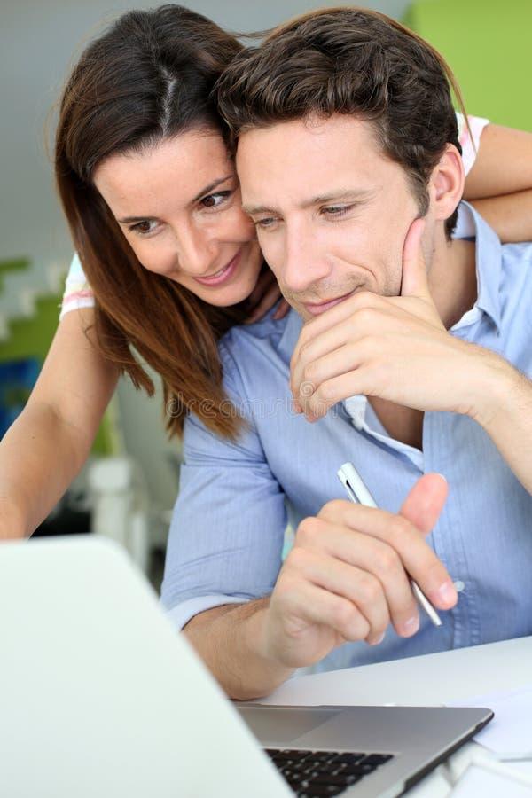 Ζεύγος που εξετάζει στο σπίτι το lap-top από κοινού στοκ εικόνα με δικαίωμα ελεύθερης χρήσης