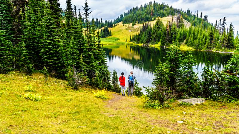 Ζεύγος που εξετάζει τη λίμνη Tod κοντά στην κορυφή του βουνού Tod Π.Χ. στον Καναδά στοκ φωτογραφίες