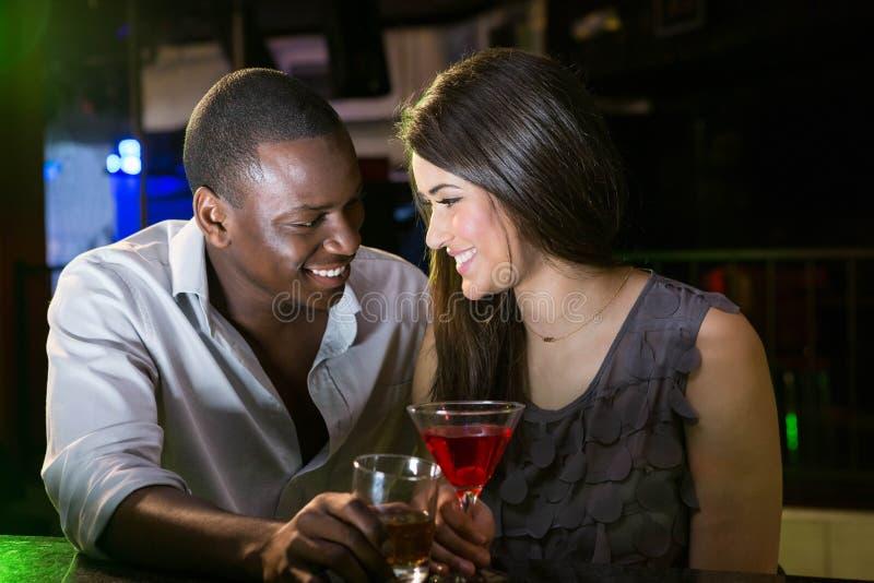 Ζεύγος που εξετάζει το ένα το άλλο και που χαμογελά ενώ έχοντας τα ποτά στοκ εικόνα με δικαίωμα ελεύθερης χρήσης