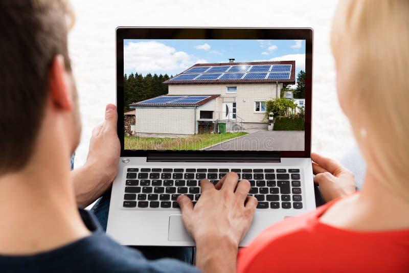 Ζεύγος που εξετάζει το σπίτι στο lap-top στοκ εικόνες