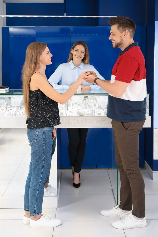 Ζεύγος που επιλέγει το δαχτυλίδι αρραβώνων στο κόσμημα στοκ φωτογραφία με δικαίωμα ελεύθερης χρήσης