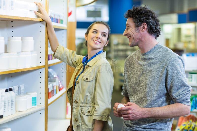 Ζεύγος που ελέγχει μια ιατρική στο ράφι στο φαρμακείο στοκ φωτογραφία με δικαίωμα ελεύθερης χρήσης