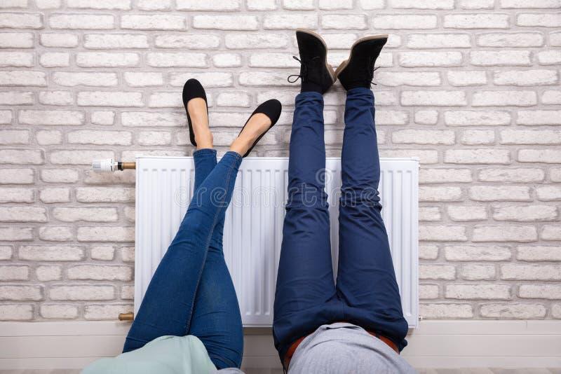 Ζεύγος που θερμαίνει τα πόδια τους στο θερμαντικό σώμα στοκ εικόνες